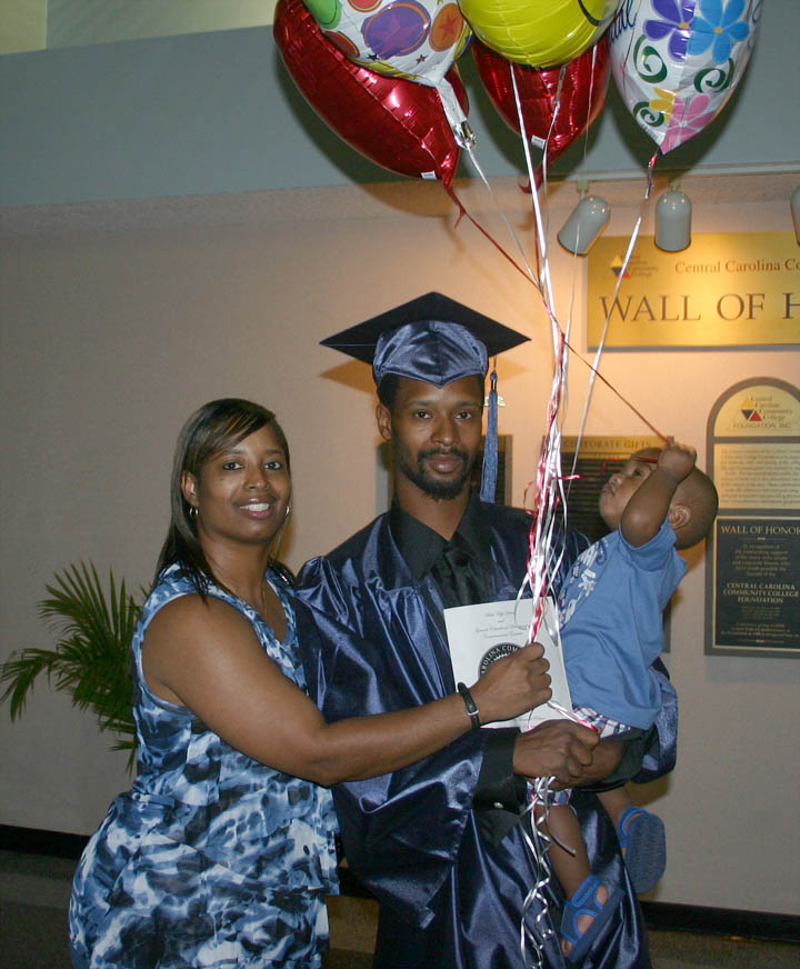 Click to enlarge,  Donna Covington (left) is all smiles as she congratulates her son, O'Brien Davis, of Lee County (center), for receiving his General Education Development diploma at the June 16 Central Carolina Community College Adult Education Department's Adult High School/GED graduation. His son, Onyx Davis, is more impressed with the congratulatory balloons the family brought. Davis was the first graduate of a college GED program held at Emmanuel Glory Church of God, in Sanford. He plans to continue his education in the college's Industrial Systems Technology program.