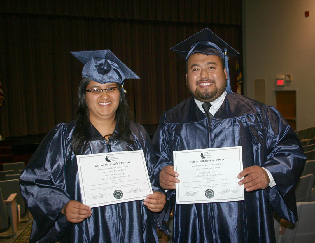 Click to enlarge,  Rosa Cornejo (left) and husband Daniel Cornejo, of Harnett County, celebrated a double milestone at Central Carolina Community College's June 16 Adult High School/GED graduation exercises. Both received their GED diplomas and plan to continue their education at CCCC, making good use of the vouchers they are holding for a free class at the college. Rosa plans to enroll in the pre-nursing program and Daniel, in automotive technology. A total of 143 students completed their AHS or GED studies during the spring semester.