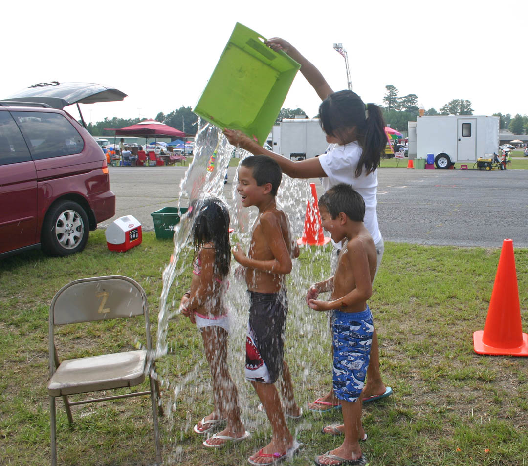 Click to enlarge,  Central Carolina Community College threw its 50th Anniversary kickoff celebration July 23 at the college's Emergency Services Training Center with fun activities, music, skill demonstrations, and fireworks. Zhyra Barber, of Sanford, gives her children (from left) Madison, Tyler and Colin, a refreshing cool-off from the 100-degree weather with a soaking at the water-balloon booth. For more about the continuing celebration during the anniversary year, visit  www.cccc.edu/50years .