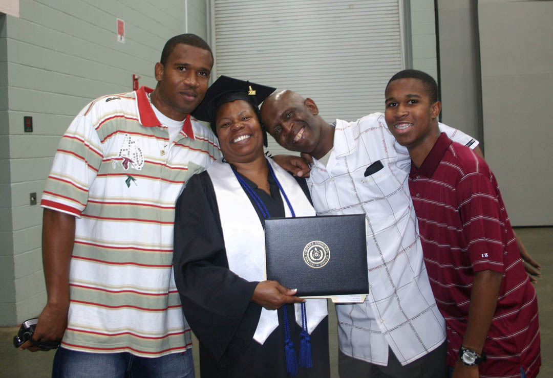 Click to enlarge,  Juanita McKinnon (second from left), of Harnett County, shares the joy of her graduation with her family, (from left) son Albert McKinnon Jr., husband, Albert McKinnon Sr., and son Bejuana McKinnon. McKinnon received her Certificate in Early Childhood Education. She was one of about 200 CCCC students who completed their studies during the summer semester.