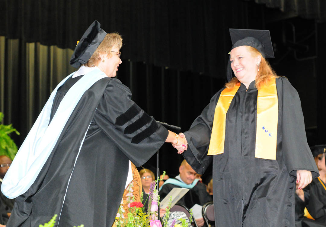 Click to enlarge,  Samantha Taylor (right), of Lee County, receives congratulations from Central Carolina Community College Vice President for Academic Affairs Lisa Chapman during the college's Summer Commencement exercises Thursday at the Dennis A. Wicker Civic Center. Taylor received her Associate in Applied Science in Office Administration. She was one of about 200 CCCC students who completed their studies during the summer semester.