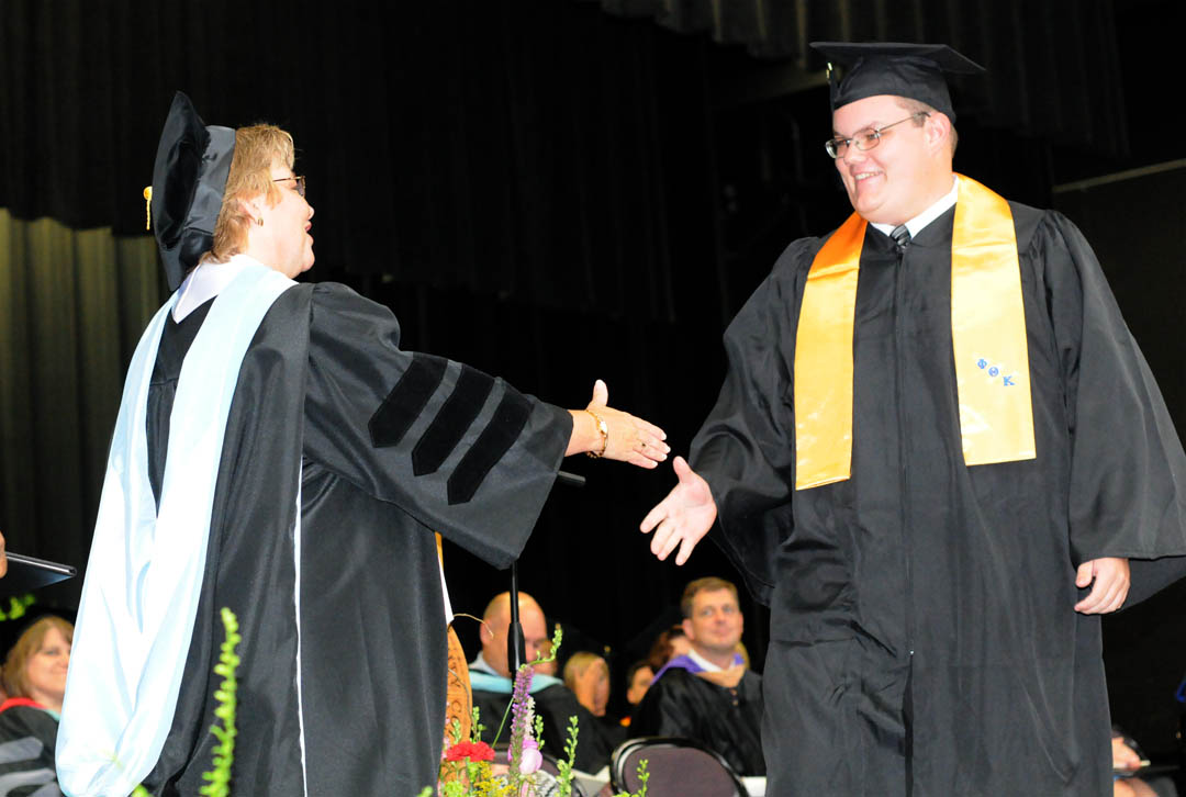 Click to enlarge,  Jeffery Grant Rosser (right), of Lee County, receives congratulations from Central Carolina Community College Vice President for Academic Affairs Lisa Chapman during the college's Summer Commencement exercises Thursday at the Dennis A. Wicker Civic Center. Rosser received his Associate in Applied Science in Mechanical Engineering Technology, with honors. He plans now to enroll in the college's Firefighter Academy. Rosser was one of the student graduation speakers. He was one of about 200 CCCC students who completed their studies during the summer semester.