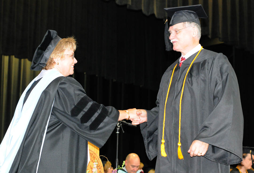Click to enlarge,  Kenneth Laughinghouse (right), of Lee County, receives congratulations from Central Carolina Community College Vice President for Academic Affairs Lisa Chapman during the college's Summer Commencement exercises Thursday at the Dennis A. Wicker Civic Center. Laughinghouse received his Associate in Applied Science in Paralegal Technology. She was one of about 200 CCCC students who completed their studies during the summer semester.