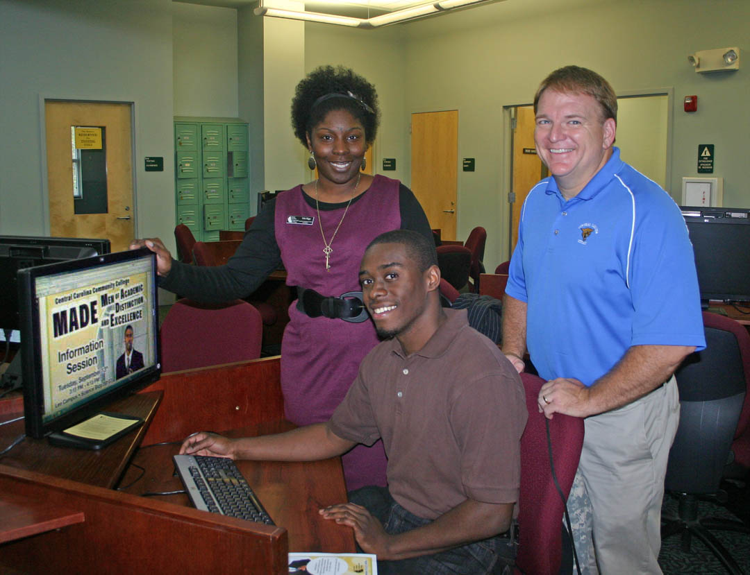 Click to enlarge,  Central Carolina Community College has received a $15,000 grant from the North Carolina Community College's Minority Male Mentoring program to implement its new MADE (Men of Academic Distinction and Excellence) Scholars program to provide assessment, outreach, guidance and support to minority male students. The program, developed by the college's Student Learning Support Department, is expected to increase minority male transition rates from developmental to curriculum courses, increase retention and graduation rates, and increase the number who transfer to four-year colleges and universities. Checking out the ad for it at the college's web page are Justin Turner (seated), of Sanford, an Associate in Arts student; Talia Higgs (back left), MADE co-director and Academic Assistance Center coordinator at the college's Lee County Campus; and Carl Bryan, dean of Student Learning Support Programs. For more information, contact Higgs or Bryan at (919) 718-7505.
