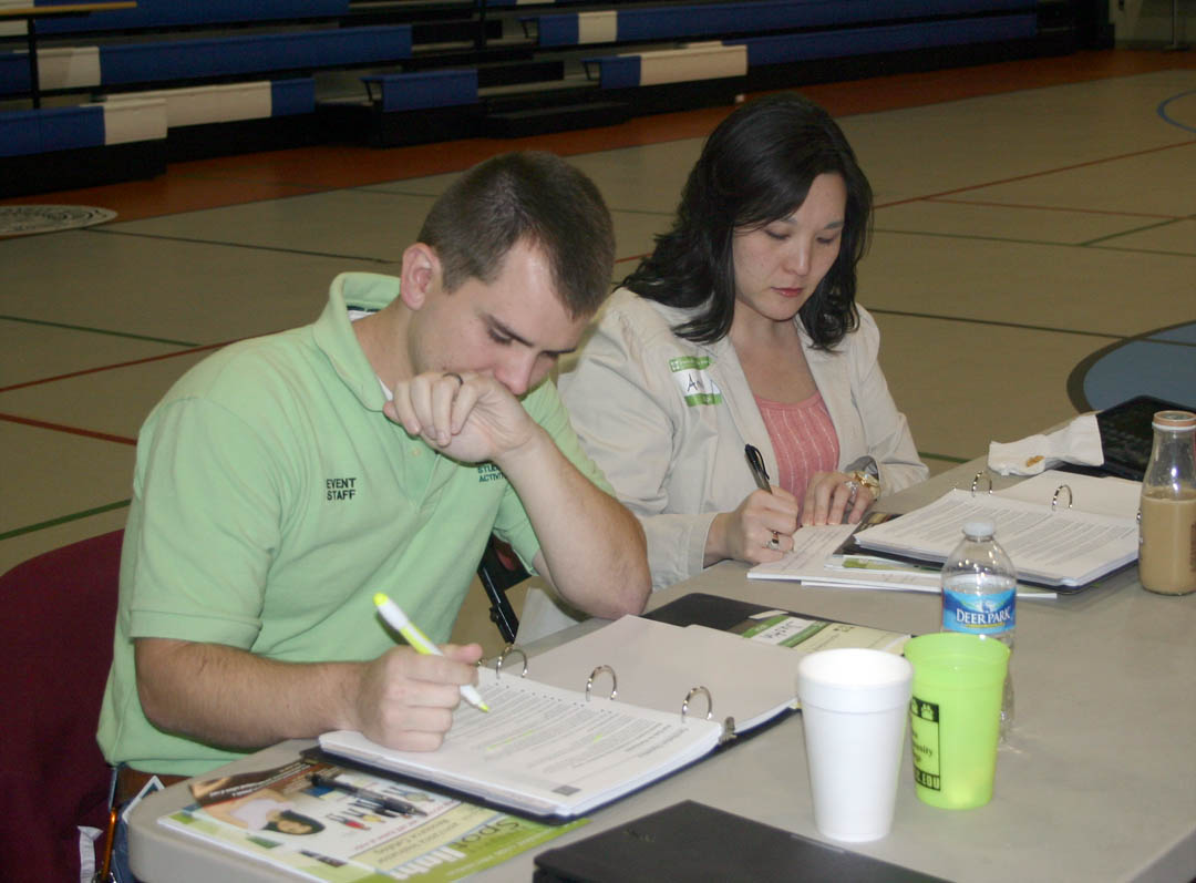 Click to enlarge,  Justin Long (left), safety director for Piedmont Community College, and Amy Noel, dean of Student Services for Sampson Community College, study their workbooks during the Oct. 24-26 Nonviolent Crisis Intervention Training 'Train the Trainer' workshop at Central Carolina Community College's Lee County Campus. Seventeen representatives from 13 North Carolina community colleges were certified as NCIT trainers to go back to their campuses and share these skills with their faculty and staff. The goal is to have those working with students prepared with nonviolent crisis intervention skills to defuse crises that might result from an out-of-control student or other person on the campus.