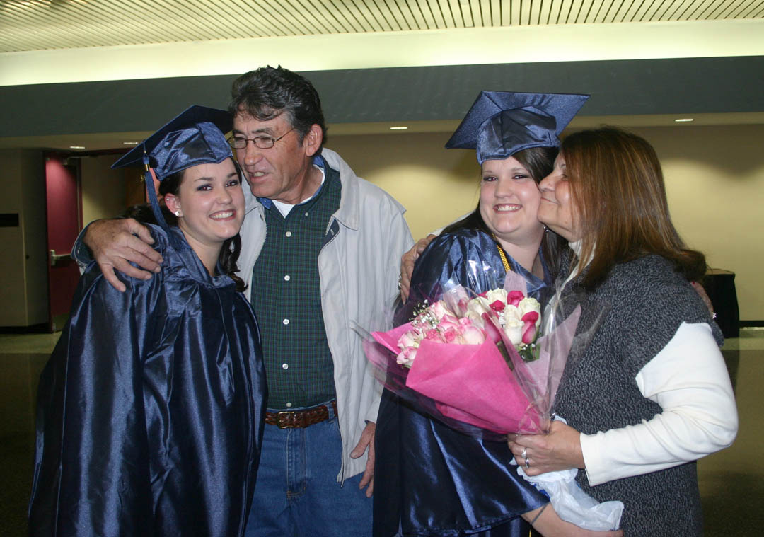 Click to enlarge,  Twins Jessica Hodges (left), and Kimberly Hodges, both of Lee County, receive big hugs from their grandfather, Danny Norton (center left), and grandmother, Dorothy Norton (right), of Laurel Hill, at Central Carolina Community College's Adult High School and General Educational Development commencement exercises Thursday, Jan. 19, at the Dennis A. Wicker Civic Center. Both received their high school diplomas and plan to continue their education in CCCC's cosmetology program.