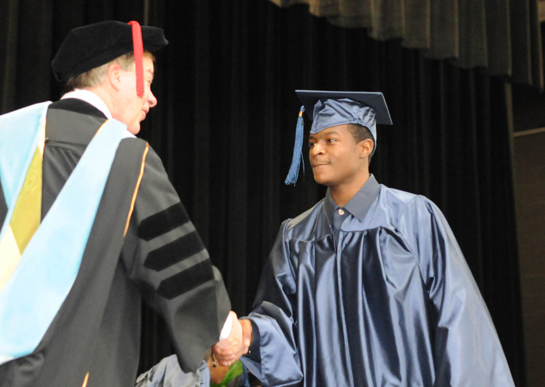 Click to enlarge,  Central Carolina Community College President Bud Marchant (left) congratulates Kiante Fox, of Lee County, on receiving his GED diploma during CCCC's College and Career Readiness Department's Adult High School and General Educational Development graduation Thursday, Jan. 19, in the Dennis A. Wicker Civic Center. Fox, an honors graduate, has already enrolled in the college's mechanical engineering program. He plans to earn an associate degree and then go on to a university.