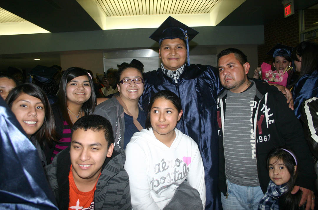 Click to enlarge,  Saul Alvarez (in cap and gown), of Lee County, and his family are all smiles following Central Carolina Community College's Adult High School and General Educational Development commencement exercises Thursday, Jan. 19, in the Dennis A. Wicker Civic Center. Alvarez received his GED and is already continuing with his education by enrolling in the college's automotive mechanics program.