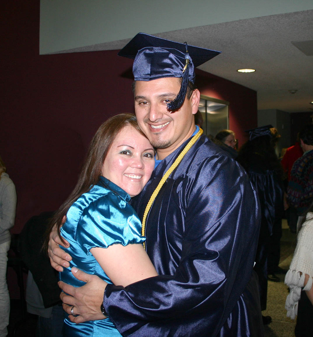 Click to enlarge,  Miguel Olvera (left) gets a congratulatory hug from his wife, Ereniva, following Central Carolina Community College's Adult High School and General Educational Development programs graduation Thursday, Jan. 19, in the Dennis A. Wicker Civic Center. Olvera earned a GED and plans to continue his education. Ereniva is a student in the college's English as a second language program.