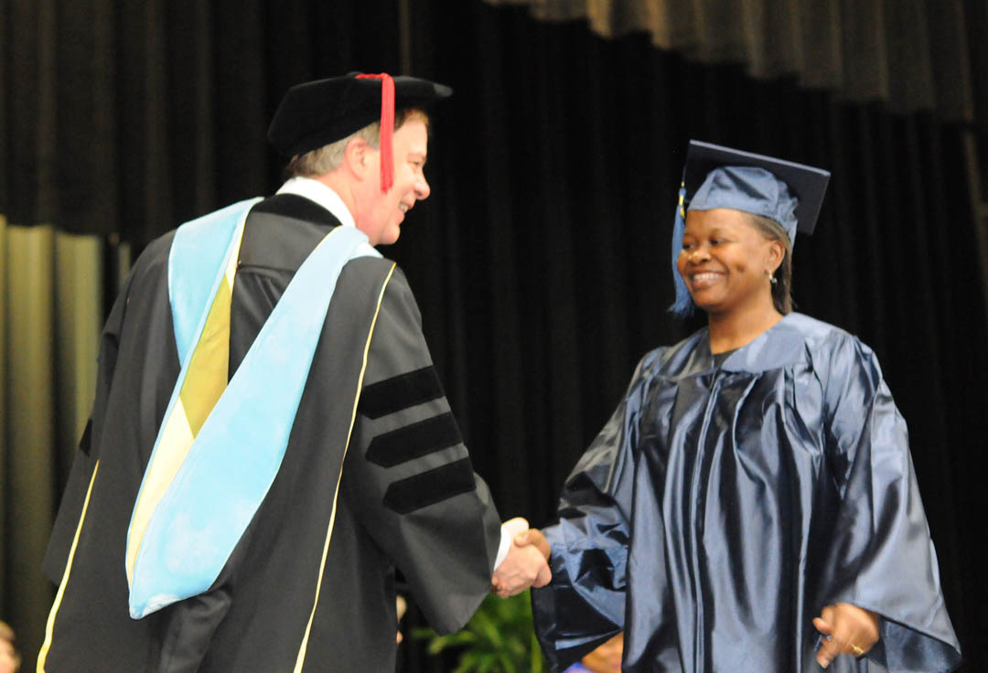 Click to enlarge,  Central Carolina Community College President Bud Marchant (left) congratulates Elizabeth Covington, of Harnett County, at the Adult High School and General Educational Development commencement exercises Thursday, Jan. 19, in the Dennis A. Wicker Civic Center. Covington, a mother of three, earned her high school diploma. She was an honors graduate and one of three student commencement speakers.
