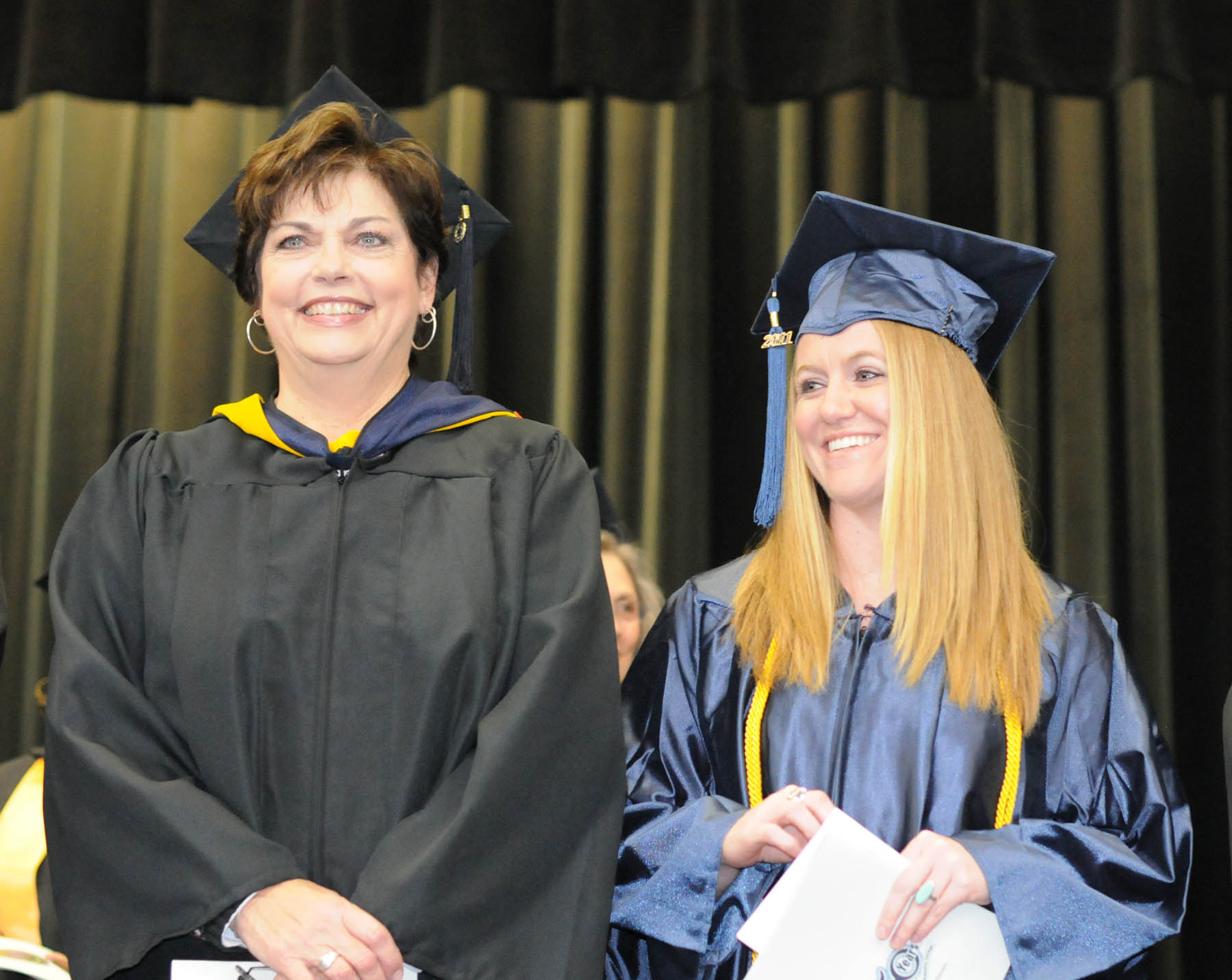 Click to enlarge,  Sara Lambert (left) Chatham County College and Career Readiness coordinator for Central Carolina Community College, and Anna Umberger, of Chatham County, are all smiles as they await the beginning of the college's Adult High School and General Educational Development programs graduation Thursday, Jan. 19, in the Dennis A. Wicker Civic Center. Umberger, an honors graduate and one of the commencement speakers, said she served a five-year mission in Honduras, where she learned to appreciate the educational opportunities available to her in the United States.