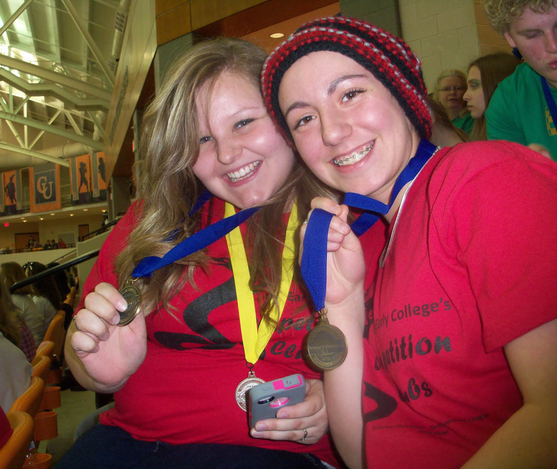 Click to enlarge,  Lee Early College students Payton Fowler (left) and Stephanie Milosh are all smiles as they display their first-place medals from the Feb. 18 Regional Science Olympiad Competition, held at Campbell University. The students competed in 'Write It, Do It,' an event that required one team member to describe a constructed object in writing. Her partner then had to build the object using only the written description. LEC's 17-member Science Olympiad team took second place overall at the competition, earning the right to go on to the North Carolina State Science Olympiad Tournament in April. LEC placed in nine of the 23 regional events, earning one first-place, two second-place, three third-place and four fourth-place medals.