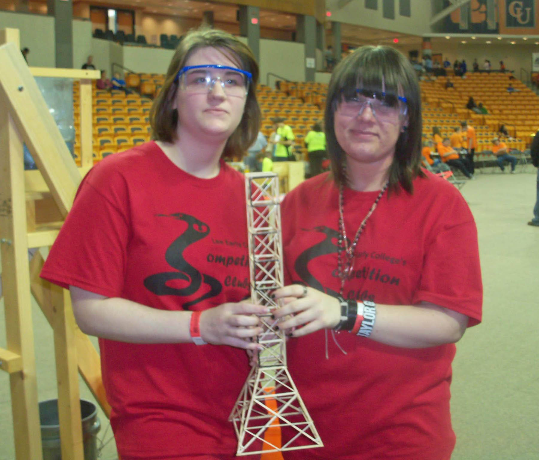 Click to enlarge,  Lee Early College students Kim Cherry (left) and Christa Rhinehart show off their second-place winning tower for the 'Towers' construction competition at the Feb. 18 Regional Science Olympiad Competition, held at Campbell University. The tower could only be constructed of wood and glue and had to be designed to hold a minimum of 15 kilograms. LEC's 17-member Science Olympiad team took second place overall at the competition, earning the right to go on to the North Carolina State Science Olympiad Tournament in April. LEC placed in nine of the 23 regional events, earning one first-place, two second-place, three third-place and four fourth-place medals.