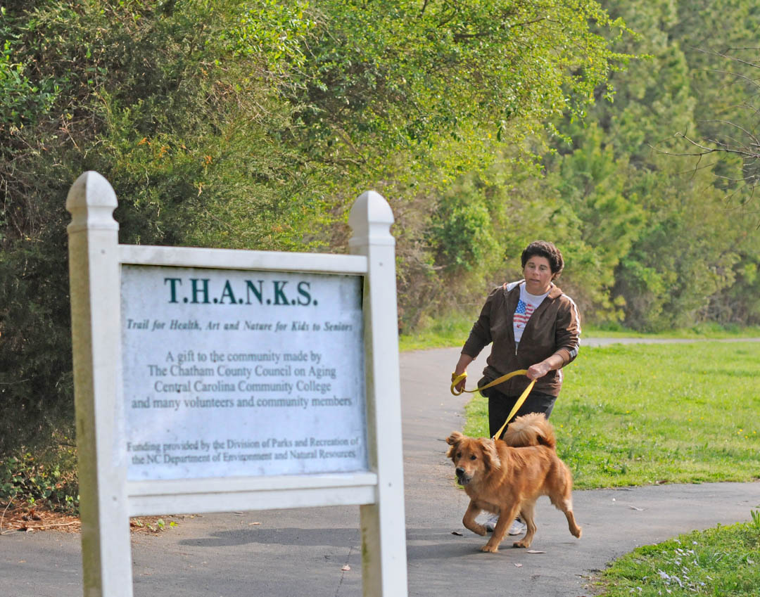 Click to enlarge,  Brenda Stecher, of Siler City, and Cheyenne, her golden retriever-chow mix pal, enjoy a walk on the Trail for Health, Art and Nature for Kids to Seniors (T.H.A.N.K.S.) walking trail at Central Carolina Community College's Chatham County Campus, in Pittsboro.   The mile-long trail circling the campus is a gift to the community by the college, Chatham County Council on Aging, and many volunteers and community members. The Division of Parks and Recreation of the N.C. Department of Environment and Natural Resources provided the funding for it. The trail is one of the healthy and fun activities available to visitors at the college's Chatham Celebration April 28 at the campus, 764 West St. Free activities run from 9 a.m.-1:30 p.m. A Health Fair will be a part of this day of fun, learning, and entertainment for the whole family. For more information and a schedule of activities, go to  www.cccc/50years/events .