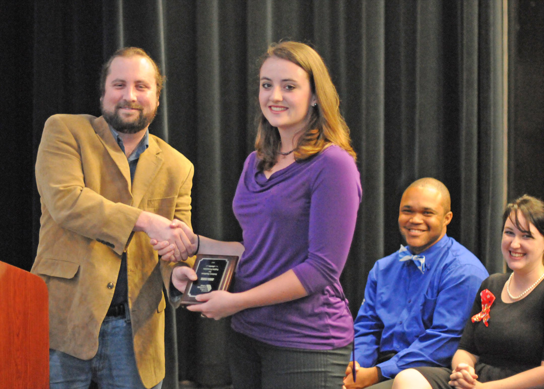 Click to enlarge,  English instructor David Watson (left) presents the Academic Excellence in English/Humanities Award to Jessica Cooper, of Lee County, at Central Carolina Community College's May 2 Academic Excellence Awards program at the Dennis A. Wicker Civic Center. Cooper also received the Outstanding Student in Spanish Award and Who's Who Among Students at America's Colleges and Universities. She was also recognized for receiving the North Carolina Community College System's Academic Excellence Award. Only one student from each of the state's 58 community colleges receives that award each year. Seated are students Samuel Headen (second from right), of Chatham County, who received the Outstanding Leadership/Inaugural Year of the Men of Academic Distinction and Excellence (M.A.D.E.) Award, and Cari Moessner, of Lee County, who received an Ambassador Service Award and Who's Who Among Students at America's Colleges and Universities. More pictures from the Academic Excellence Awards event are online at  www.cccc.edu/academicexcellencepics/ .