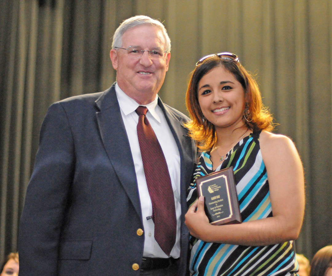 Click to enlarge,  Gary Beasley (left), lead instructor for Central Carolina Community College's Laser & Photonics Technology program, congratulates Karen Diaz, of Harnett County, for receiving the Outstanding Student in Laser & Photonics Technology Award during the college's May 2 Academic Excellence Awards program at the Dennis A. Wicker Civic Center. Diaz previously earned an A.A.S. in Electronics Engineering Technology in 2010 and received the Outstanding Student in EET that year. More pictures from the Academic Awards program are online at  www.cccc.edu/academicexcellencepics/ .