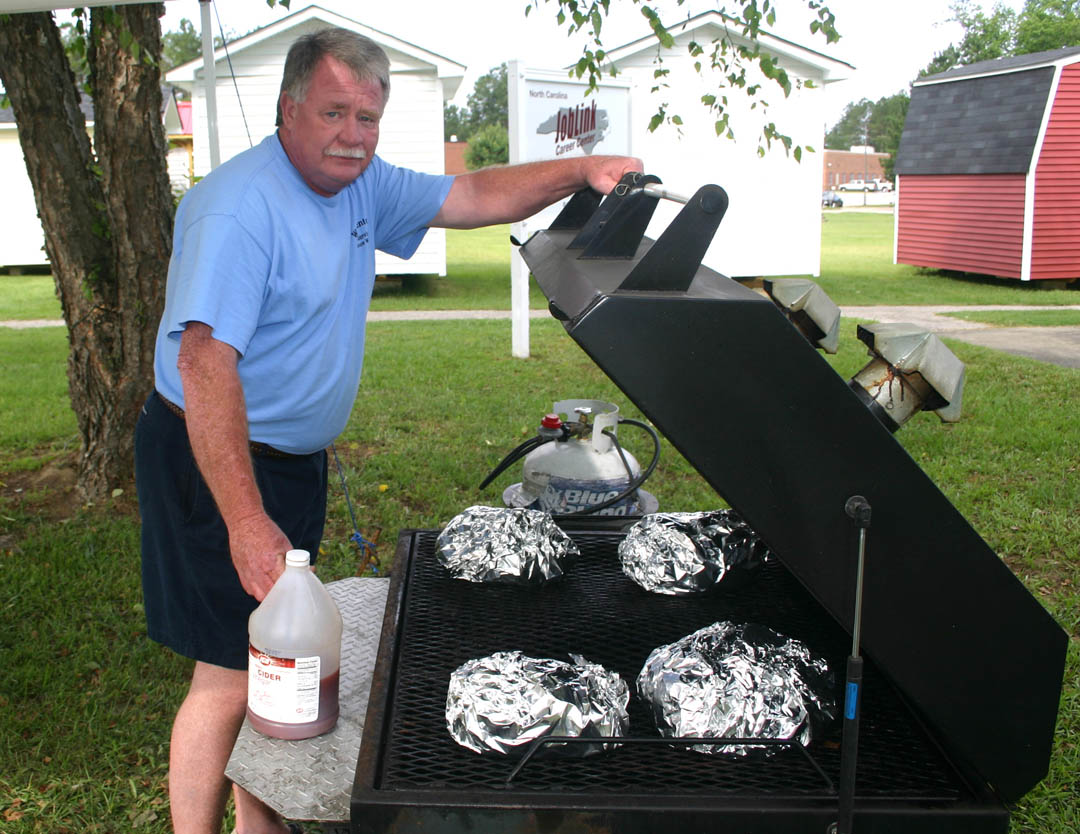 Click to enlarge,  David Whittenton, of Dunn, checks his pork barbecue prior to the judging of the Barbecue Cook-off June 2 at Central Carolina Community College's Harnett County Campus. Whittenton cooked up the winning entry. The judges described his barbecue as 'most tender; tasty but not overpowering.' The Cook-off was part of the college's 50th Anniversary Celebration. Close in the competition were the teams of Gary Hughes and Wayne Wellington, of Angier; Mark Byrd, of Coats; Nothing Butt Luv'n team of Robert and Kristy Baggett, of Lillington; and Eddie Who's BBQ team of Eddie Stanley, of Benson, and Jeff Blackman, of Lillington.