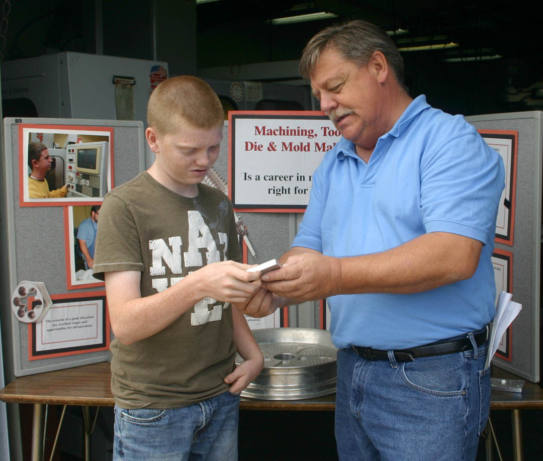 Click to enlarge,  Thirteen-year-old Josh Currin (left), of Mamers, gets a description of how an aluminum cutout of the Peanuts cartoon dog Snoopy was made in the college's Machining Technology Department. The department was part of the college's 50th Anniversary Celebration June 2 at the Harnett County Campus, commemorating its start in 1961 in Lee County and its expansion into Harnett in 1965.