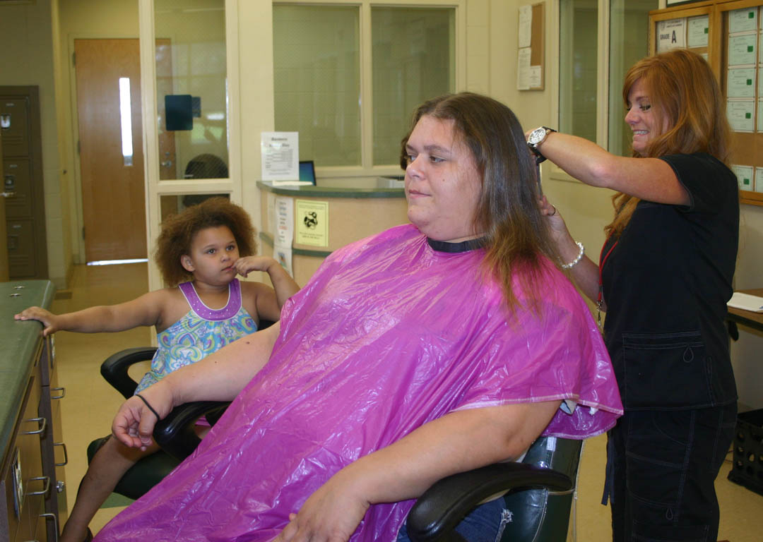Click to enlarge,  Shauna Warren (center), of Erwin, gets a trim from Central Carolina Community College Advanced Cosmetology student Angela Cashwell (right), of Coats, as Warren's daughter, Serenity, watches. The hair trim was one of the services offered to visitors during the college's 50th Anniversary Celebration June 2 at the Harnett County Campus. The event commemorated its start in 1961 in Lee County and its expansion into Harnett in 1965.  Warren, a Certified Nurse Aide, graduated from the CNA program at the Harnett Campus in 1998.