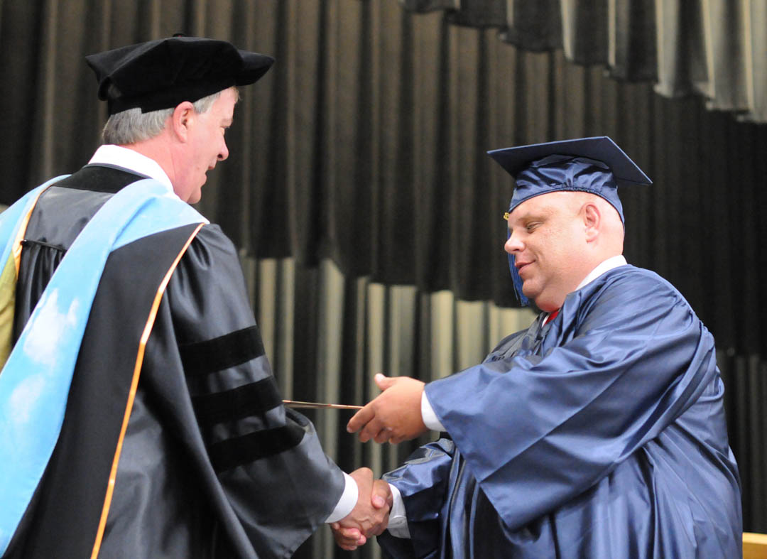 Click to enlarge, Central Carolina Community College President Bud Marchant (left) congratulates Herbert Taylor, of Lee County, on receiving his GED diploma during the College and Career Readiness Department's Adult High School and General Educational Development Commencement Exercises Thursday, June 14, in the Dennis A. Wicker Civic Center. Taylor was also one of three student commencement speakers.