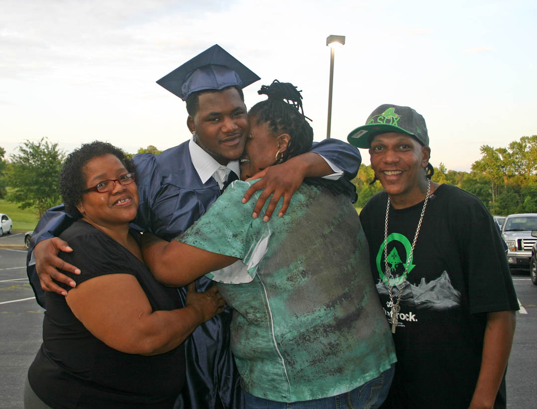 Click to enlarge, LaKuan McKoy (second from left), of Lee County, receives big hugs and congratulations from (from left) his grandmother, Cathy Reid; mother, Tina Reid; and family friend Bryont Fields, following Central Carolina Community College's Adult High School and General Educational Development commencement exercises Thursday, June 14, at the Dennis A. Wicker Civic Center. McKoy earned his high school diploma and plans to continue his education at the college.