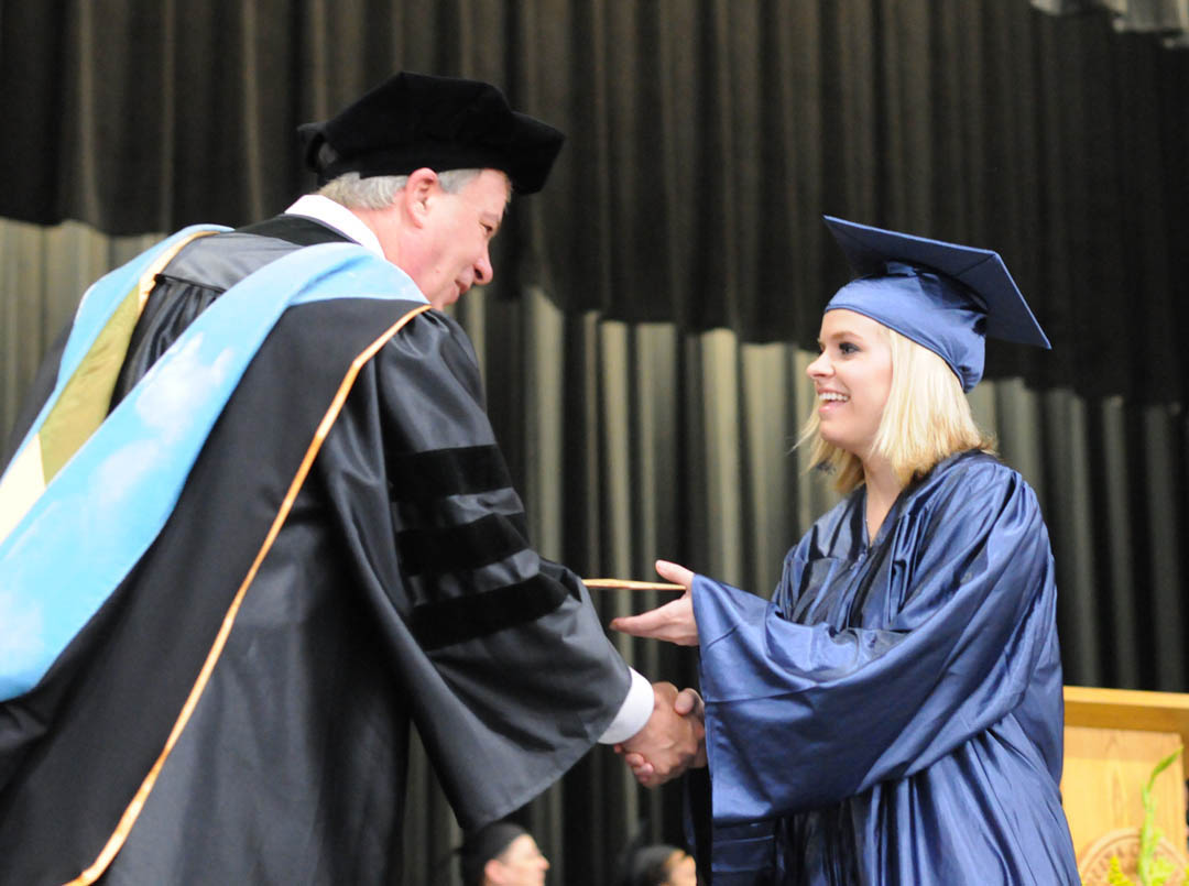 Click to enlarge, Rachel Umberger (right), of Chatham County, receives her GED diploma from Central Carolina Community College President Bud Marchant during the Adult High School and General Educational Development Commencement Exercises Thursday, June 14, in the Dennis A. Wicker Civic Center. She was also one of the three student commencement speakers.