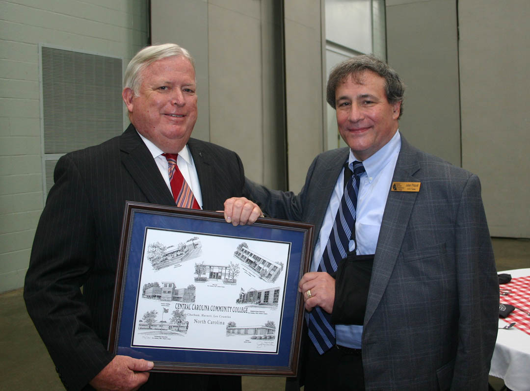 Click to enlarge,  Ed Garrison (left), of Sanford, a Central Carolina Community College trustee from 2004 to 2012, was honored at a July 25 dinner at the Dennis A. Wicker Civic Center. He was presented with a Jerry Miller drawing of buildings on the college's campuses in Chatham, Harnett and Lee counties. CCCC Board of Trustees Chair Julian Philpott (right) thanks Garrison for his service. Garrison continues his service to the college through the CCCC Foundation Board of Directors. He has sat on that board for more than 20 years.