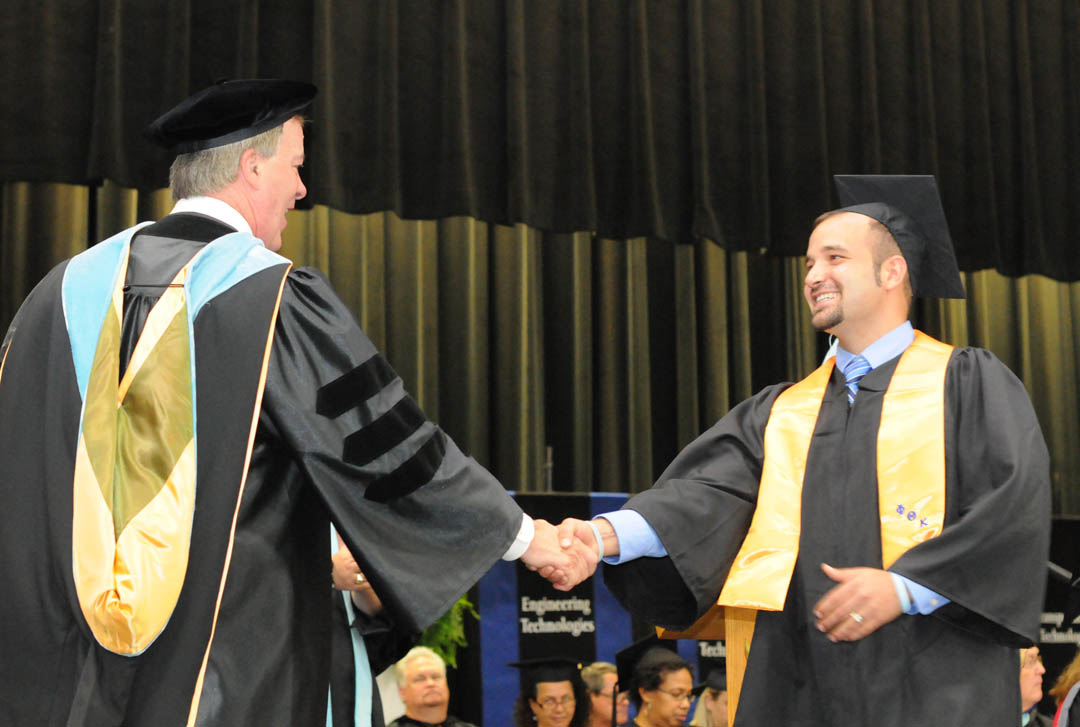 Click to enlarge,  Central Carolina Community College President Bud Marchant (left) congratulates Steven Richard, of Chatham County, on receiving his Associate of Arts degree during the college's Aug. 2 Summer Commencement. Richard will continue his education at UNC-Chapel Hill. About 170 students completed their studies during the summer semester; 100 participated in the exercises. The graduates earned almost 300 degrees, diplomas and certificates. Some will continue their education at four-year institutions, while most will take their new skills and knowledge directly into the workforce.