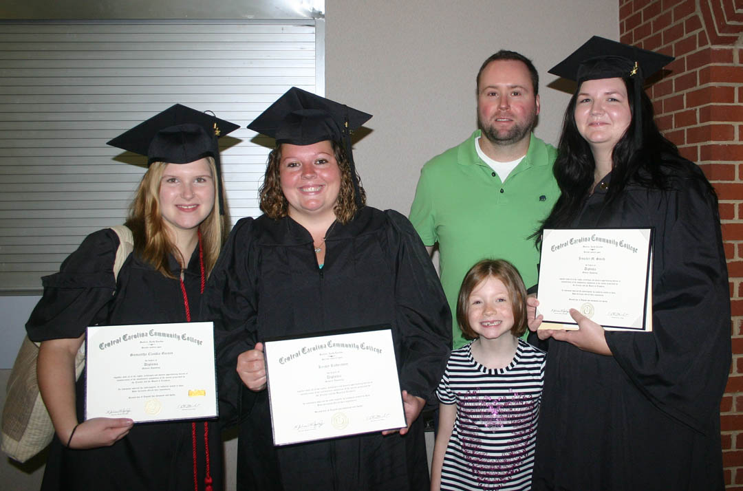 Click to enlarge,  Samantha Gaines (left), of Lee County, and Kristy Robertson (center) and Jennifer Smith, both of Chatham County, all received their Diploma in Medical Assisting during Carolina Community College's Summer Commencement Exercises Aug. 2 at the Dennis A. Wicker Civic Center. Pictured with them are Smith's daughter, Taylor, 8, and husband, Christopher. About 170 students completed their studies during the summer semester; 100 participated in the exercises. The graduates earned almost 300 degrees, diplomas and certificates. Some will continue their education at four-year institutions, while most will take their new skills and knowledge directly into the workforce.