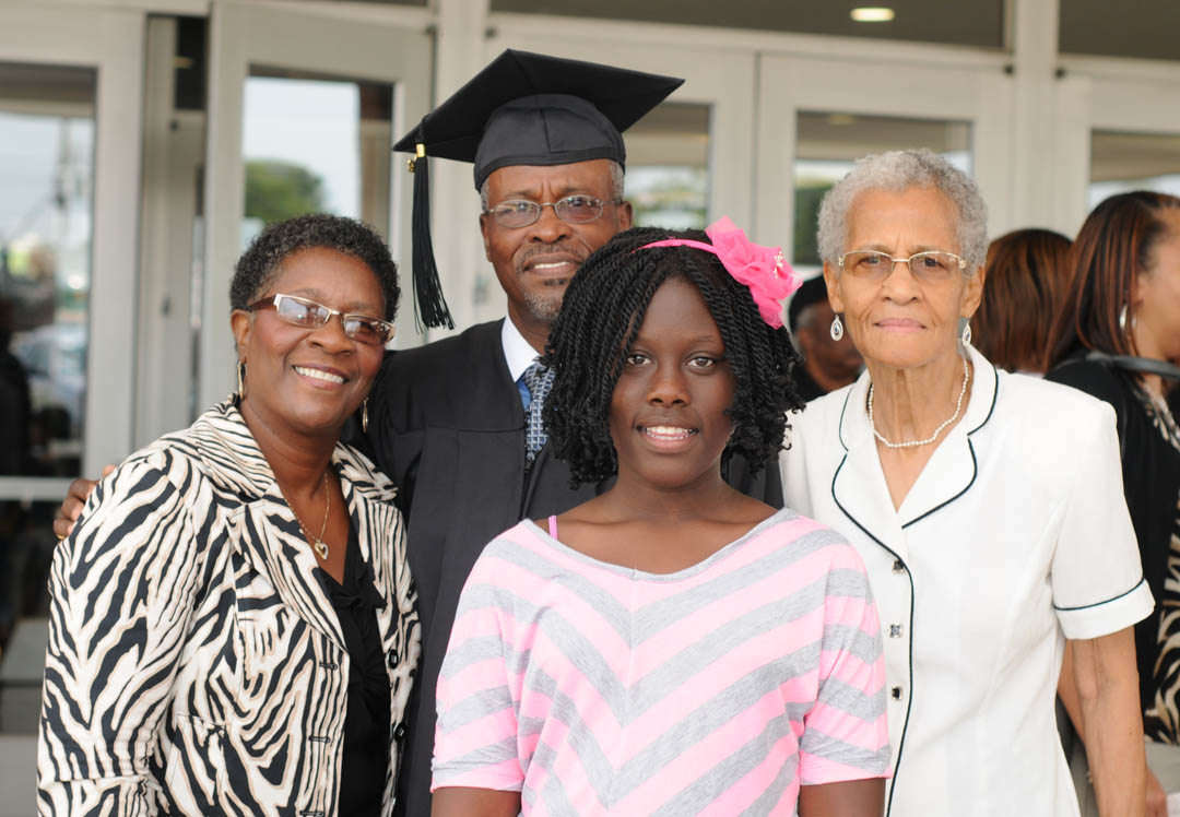 Click to enlarge,  Ernest Cross (back), of Harnett County, received his Certificate in Barbering during Carolina Community College's Summer Commencement Exercises Aug. 2 at the Dennis A. Wicker Civic Center. Sharing the special occasion with him are (front, from left) his fiancee Edna Perkins; daughter, Nyrea Cross; and mother, Verna Cross. About 170 students completed their studies during the summer semester; 100 participated in the exercises. The graduates earned almost 300 degrees, diplomas and certificates. Some will continue their education at four-year institutions, while most will take their new skills and knowledge directly into the workforce.
