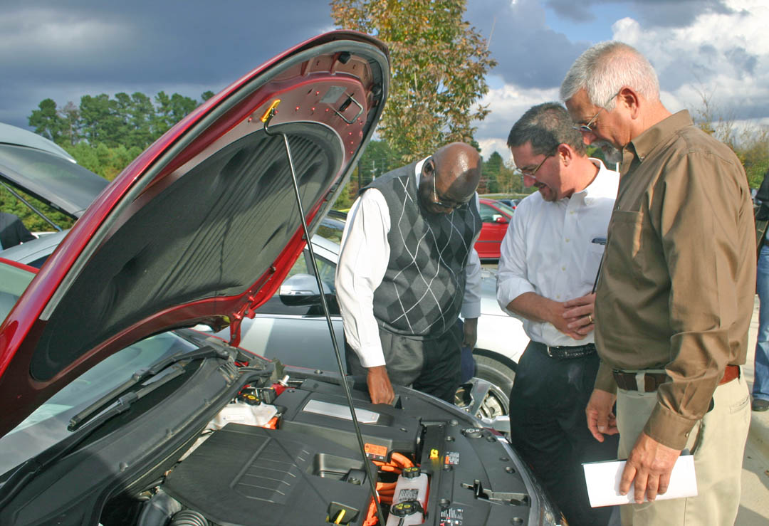 Click to enlarge,  Central Carolina Community College's Chatham County Campus, in Pittsboro, and the Triangle Clean Cities Coalition hosted a National Alternative Fuel Vehicle Day Odyssey Oct. 18. Among the activities was a display of AFVs. Checking under the hood of a Chevy Volt electric-gasoline hybrid are (from left) Sanford City Councilman J.D. Williams, Sanford Public Works Director Vic Czar, and Sanford General Services aDirector Tim Shaw. For information about sustainability programs at Central Carolina Community College, visit its Web site,  www.cccc.edu/green .