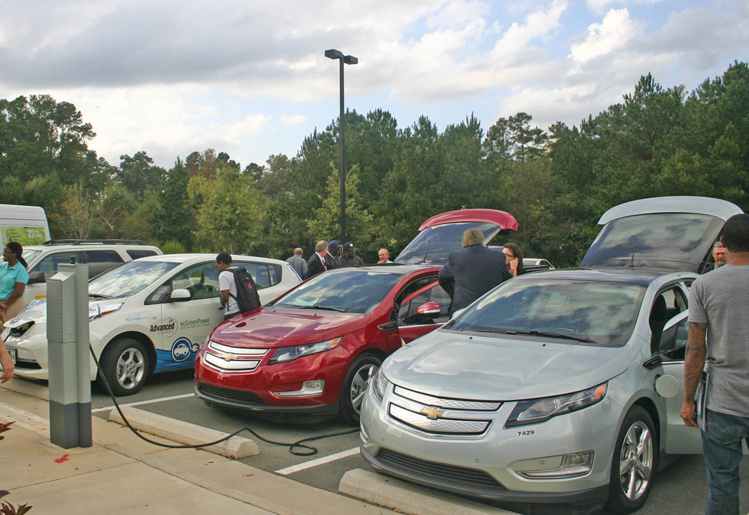 Click to enlarge,  Visitors look over vehicles powered by alternative fuels at the National Alternative Fuel Vehicle Day Odyssey Oct. 18 at Central Carolina Community College's Chatham County Campus. The college and the Triangle Clean Cities Coalition hosted the event. Vehicles on display include (from far left) CCCC's biofuels-powered van, BuildSense Inc.'s bi-fuel CNG-gasoline Ford Escape, Advanced Energy Corp.'s all-electric Nissan Leaf, and Wilkinson Cadillac-Chevrolet-Buick-GMC and Duke Energy's electric-gasoline hybrid Chevy Volts. For information about sustainability programs at Central Carolina Community College, visit its Web site,  www.cccc.edu/green .