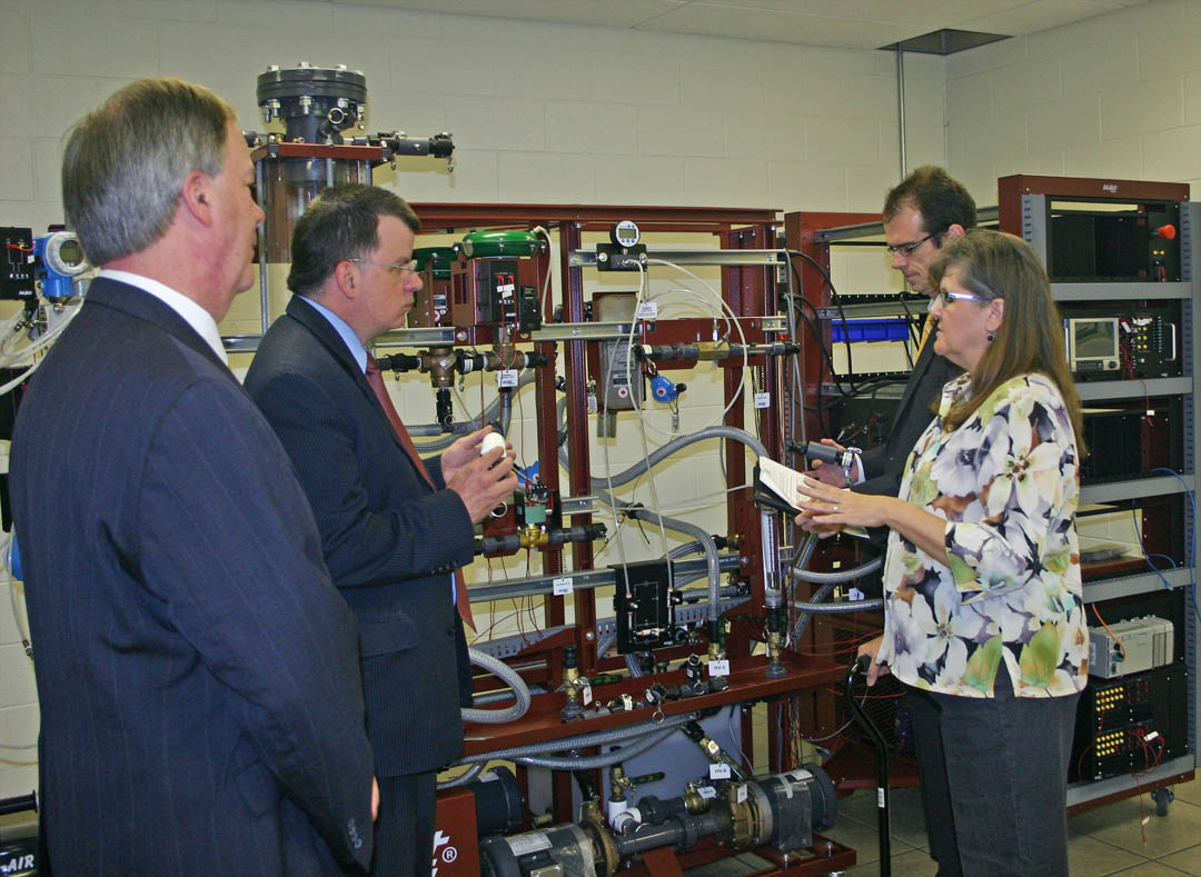 Click to enlarge,  Central Carolina Community College President Bud Marchant (left); Dan Gerlach, president of the Golden LEAF Foundation, and Ted Lord (back right), vice president of programs/staff attorney for the Foundation, look over the hydraulics station in CCCC's Industry Training Center as Cathy Swindell, CCCC Industry Services director, explains the training workers receive on the equipment. A $447,000 grant from the Golden LEAF Foundation paid for the equipment in the ITC's welding shop and industry skills lab, including the hydraulics station. Gerlach and Lord visited Nov. 13 to see the impact of the grant. The ITC is located in the Innovation Center at the Lee County Industrial Park.