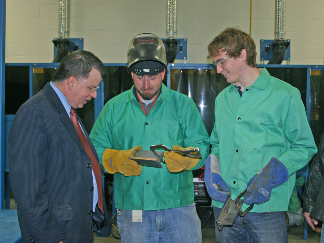 Click to enlarge,  Dan Gerlach (left), president of the Golden LEAF Foundation, talks with Caterpillar employees Michael Thompson (center), endurance field test lead, and M.P. Spierer, engineer, about some of the work they do in the welding class taught for the company at Central Carolina Community College's Industry Training Center. A $447,000 grant from the Foundation provided the equipment in the ITC's welding shop and industry skills lab. Gerlach and Ted Lord (not pictured), vice president of programs/staff attorney for the Foundation, visited Nov. 13 to see the impact of the grant. The ITC is located in the Innovation Center at the Lee County Industrial Park.