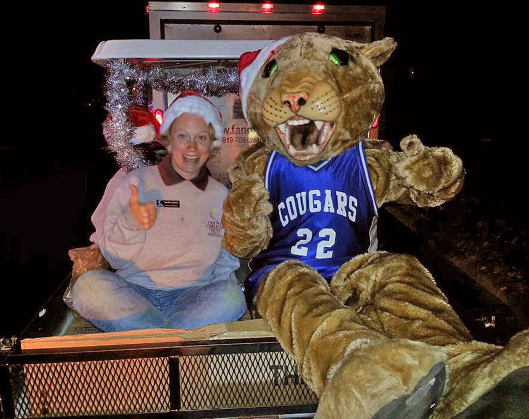 Click to enlarge,  Charlee Cougar (right), Central Carolina Community College's mascot, joins CCCC Ambassador Jennifer Sanford Johnson, of Raleigh, for a ride in the Dec. 3 Sanford Christmas Parade. Inside that furry suit is sophomore David Green, who enjoys adding fun to college and community events. Green, a second-year Criminal Justice student, is a decorated combat veteran who served in Afghanistan in 2009. He jokes that his tour of duty in the Middle East has made it easy for him to endure the internal 125-degree temperature that the Charlee costume can reach after being worn for a while.