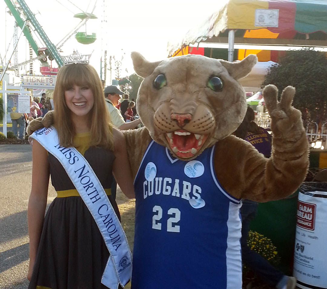 Click to enlarge,  Miss North Carolina 2012, Arlie Honeycutt (left), of Garner, visited the Lee County Fair in September and enjoyed meeting Charlee Cougar, Central Carolina Community College's mascot. Inside that furry suit is sophomore David Green, who likes adding fun to college and community events. Green, a second-year Criminal Justice student, is a decorated combat veteran who served in Afghanistan in 2009. He jokes that his tour of duty in the Middle East has made it easy for him to endure the internal 125-degree temperature that the Charlee costume can reach after being worn for a while.