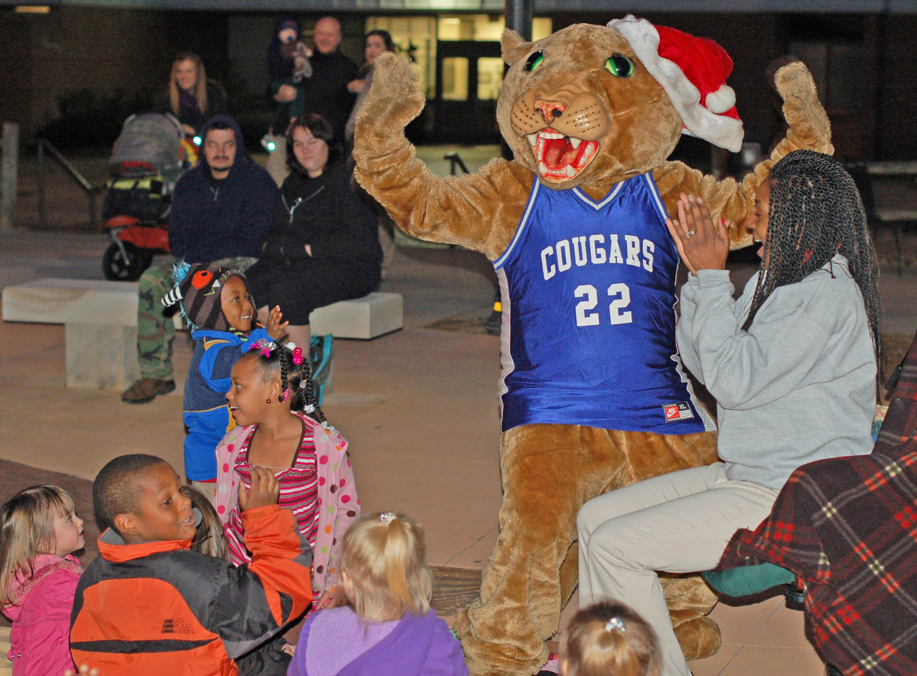 Click to enlarge,  Charlee Cougar (center), Central Carolina Community College's mascot, delights the children and college Ambassador Narrie Liverman (right), of Angier, during the college's Dec. 6 Christmas Tree Lighting event at the Lee County Campus, in Sanford. Inside that furry suit is sophomore David Green, who enjoys adding fun to college and community events. Green, a second-year Criminal Justice student, is a decorated combat veteran who served in Afghanistan in 2009. He jokes that his tour of duty in the Middle East has made it easy for him to endure the internal 125-degree temperature that the Charlee costume can reach after being worn for a while.
