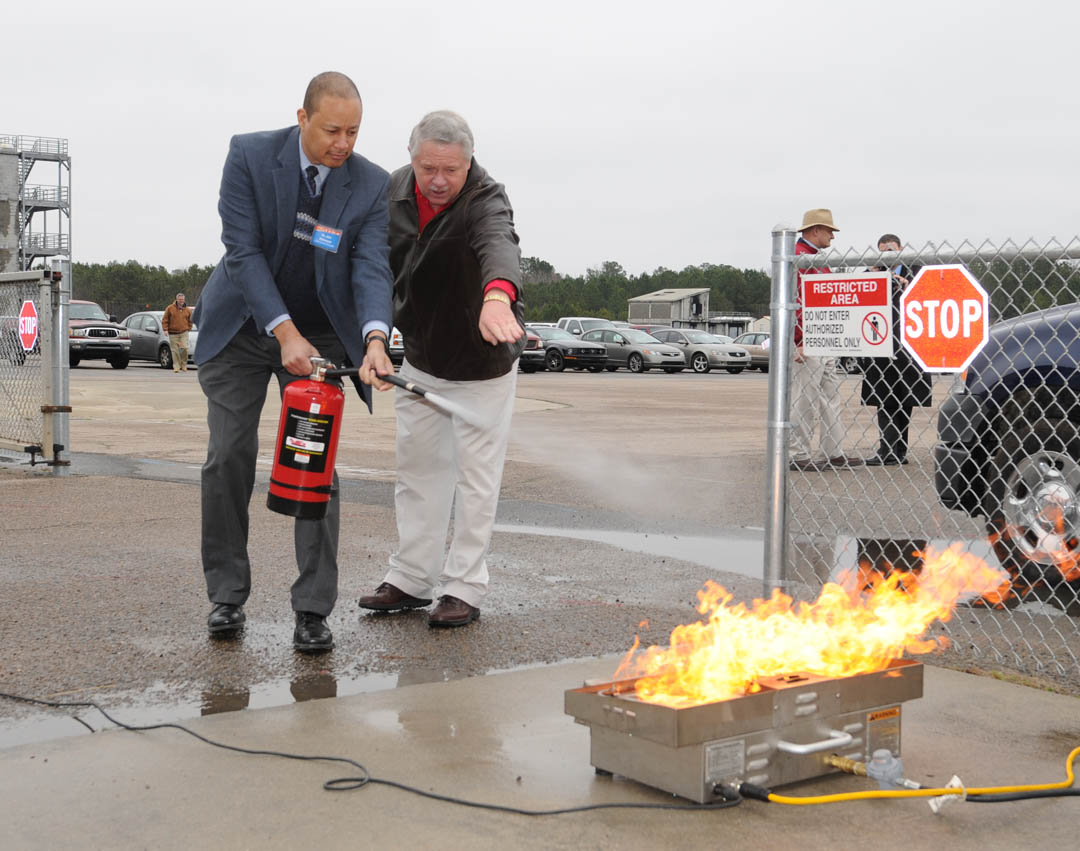 Click to enlarge,  Dr. Jim Atkinson (left), assistant superintendent for Auxiliary Services for Lee County Schools, gets a lesson in extinguishing a fire from Joey Shue, Central Carolina Community College's Fire and Rescue coordinator.