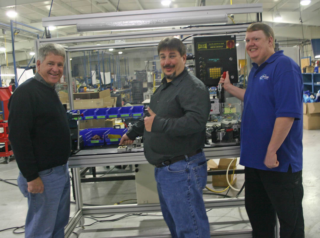 Click to enlarge,  Jerry Pedley (left), founder and president of Mertek Solutions, in Sanford, and two of his employees, Jeff Spivey, of Goldston, designer of mechanical assembly machines, and Craig Hart, of Gulf, designer of electrical assemble machines, check out one of the company's machines for assembling automotive parts. Pedley has a strong working relationship with Central Carolina Community College, where all his workers have received training, including Spivey and Hart. Since it opened in 2010, the company has grown to 33 employees and $4 million in annual sales. For more information about Mertek Solutions, visit  www.merteknc.com . For more information about Central Carolina Community College's engineering and industrial technologies programs and other programs, visit  www.cccc.edu .