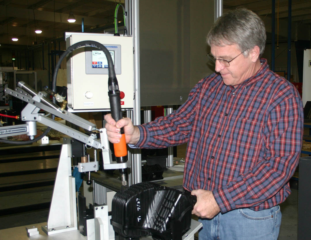 Click to enlarge,  Jerry Pedley, founder and president of Mertek Solutions, in Sanford, demonstrates one of the robotic assemblers at the company. Mertek is a globally oriented company whose engineers design and build automated testing and assembly equipment for a wide range of products in various industries. Since it opened in 2010, the company has grown to 33 employees and $4 million in annual sales. All of the company's technicians and engineers have received skill training through Central Carolina Community College's engineering and industrial technologies programs. The college's Industry Services Office also provides at-site workforce training. For more information about Mertek Solutions, visit  www.merteknc.com . For more information about Central Carolina Community College's engineering and industrial technologies programs and other programs, visit  www.cccc.edu .
