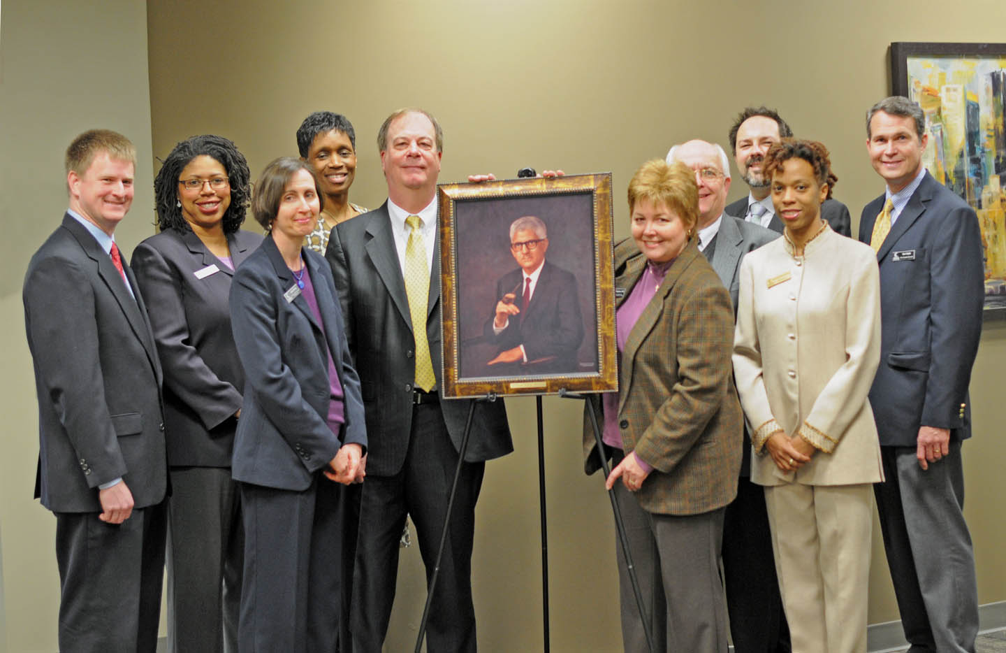 "Click to enlarge,  Central Carolina Community College's President's Council gathered for the unveiling of a portrait of Dr. W. Dallas Herring at the college's Lee County Campus. The North Carolina Community College System and the 58 community colleges across the state recognized March 6 as ""Dallas Herring Day."" The portrait, a gift from the NCCCS, commemorates the  system's 50th anniversary and Herring's vision and tireless work in promoting community colleges as institutions of comprehensive education. Pictured (from left) are Dr. Phillip Price, vice president for Administrative Services; Dr. Pam Senegal, vice president for Economic and Community Development; Celia Hurley,  vice president for Instructional Advancement; Stacey Carter-Coley, Esq., executive director of Human Resources and Ethics Liaison; Dr. Bud Marchant, president; Dr. Lisa Chapman, executive vice president for Instruction; Bill Tyson, Harnett County provost; William Messersmith (back), associate director of Human Resources; Nicole Brown, Human Resources instructor; and Ken Hoyle, vice president of Student Services."