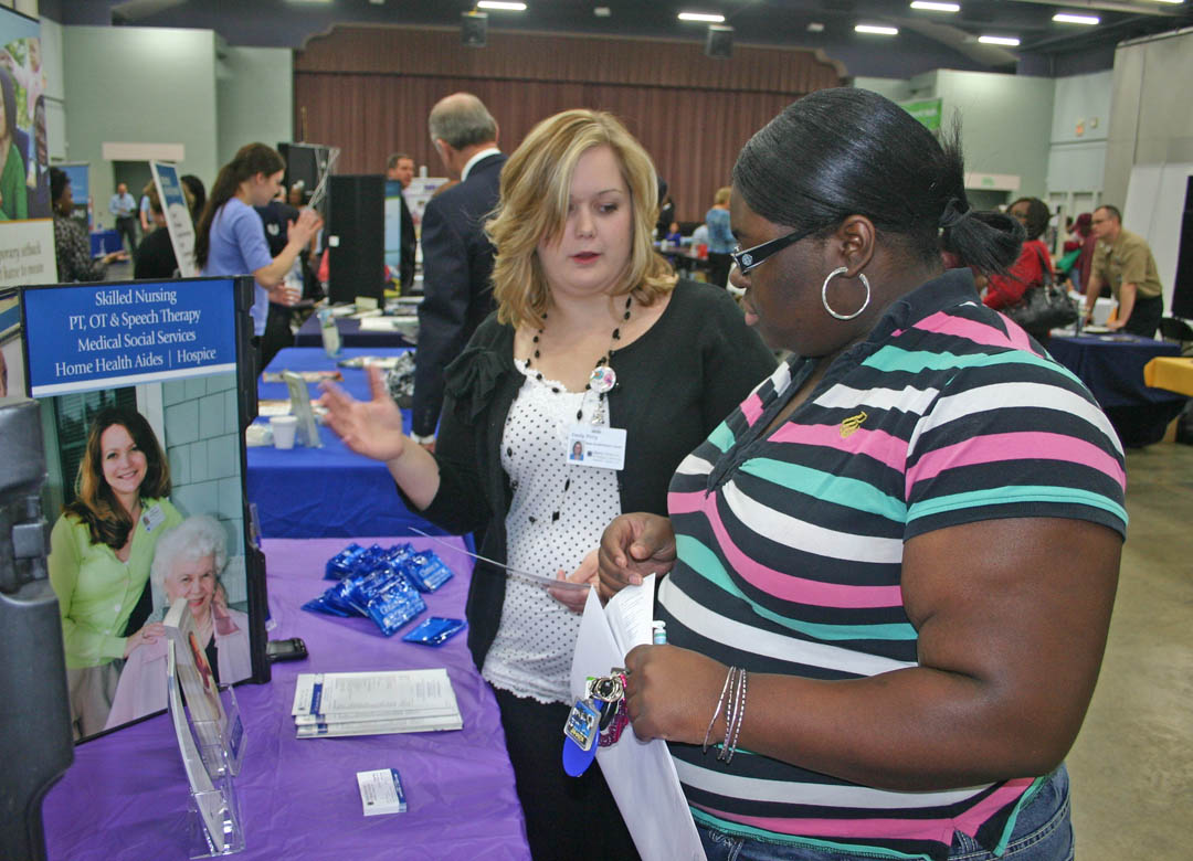 Click to enlarge,  Central Carolina Community College student Porsha Cooke (right), of Sanford, speaks with Liberty HomeCare and Hospice representative Emily Petty, of Siler City, about opportunities for employment with the company. Cooke will graduate in May with an Associate in Applied Science in Medical Office Administration. Petty graduated from CCCC in 2012, also with an A.A.S. in Medical Office Administration. The Career Fair was sponsored by the college's Career Center. For more information about the services the Center offers, call 919-718-7396 or go to www.cccc.edu/careercenter/.