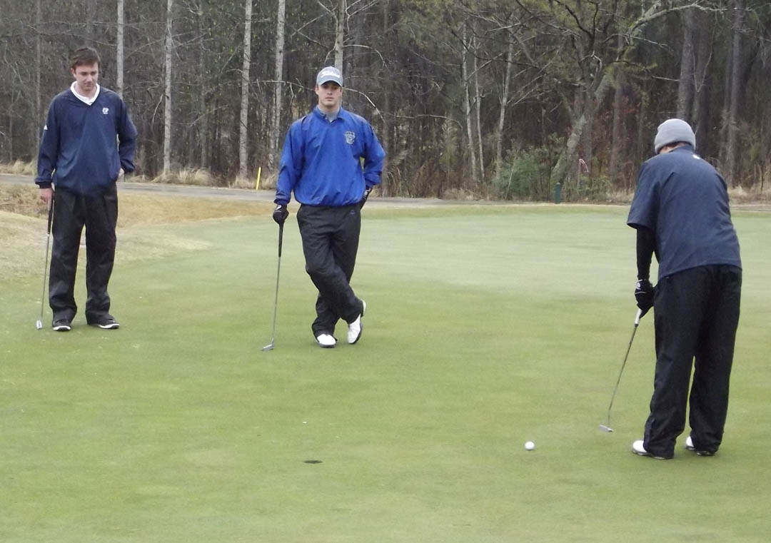 Click to enlarge,  Central Carolina Community College's Cougar Golf Team played against teams from Johnston Community College, Louisburg Community College, and Peace University April 4 at Anderson Creek Golf Course. In spite of the heavy rain, the teams played nine holes. Lacy Tripp (right), of CCCC, shoots for a short par putt on the par 3 4th hole as golfers from Louisburg and Johnston watch. The Cougars will play at the April 20-21 National Junior College Athletic Association's Division III, Region X regionals at Emerald Golf Club in New Bern. For more on CCCC sports, visit www.cccc.edu/sports.