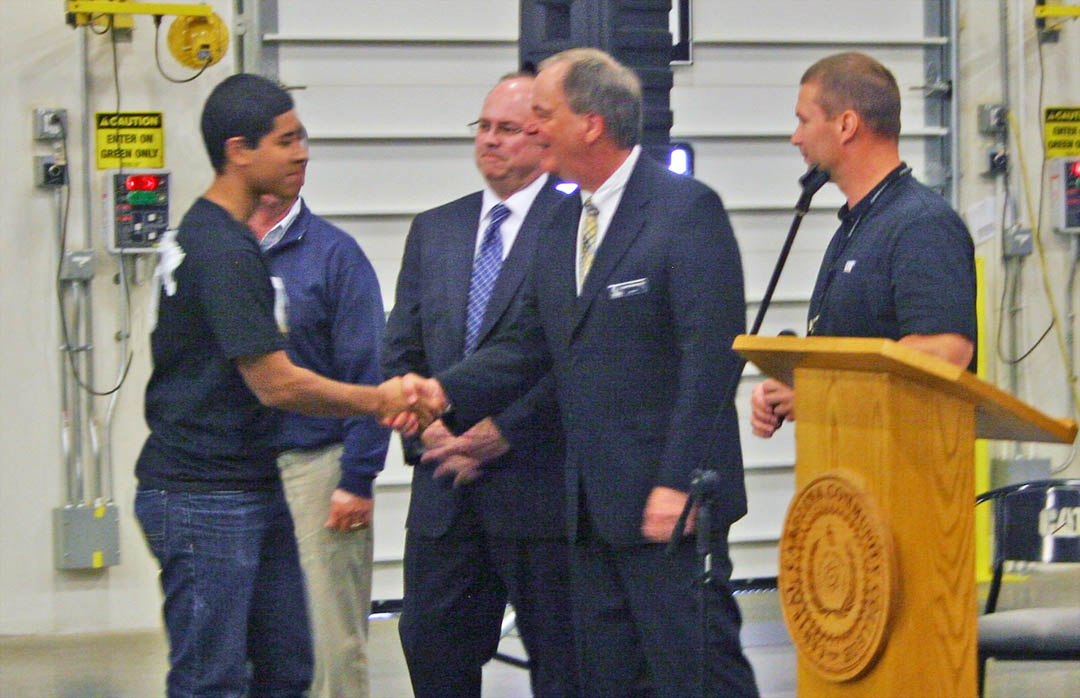 Click to enlarge,  Ellizon Torres (left), of Southern Lee High School, is congratulated by CCCC President Bud Marchant (second from right) on his May 2 induction into the Caterpillar Youth Apprenticeship Program in welding. Also congratulating Torres are Donnie Oldham (behind Torres), chair of the Lee Economic Development Committee; Dr. Andy Bryan, associate superintendent of Lee County Schools; and Martin Kegel, facility manager for Caterpillar-Sanford. Sixteen students from Lee County public high schools were inducted into the program, which trains them for a career as a welder. The students will learn their skills at the college campus, through the college's Industry Services Center at the Innovation Center in the Lee County Industrial Park, and at Caterpillar-Sanford. For information on CCCC's industry training programs, visit www.edu/ecd/departments/businessindustry/ or call the Industry Services Office at 919-718-7212.