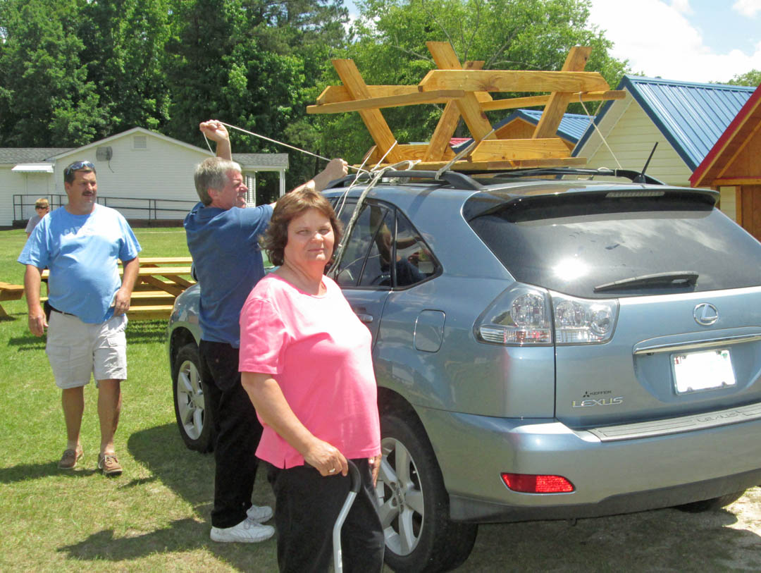 Click to enlarge,  David Maynor (back), of Dunn, and his wife, Sharon (front) get a helping hand from Anthony Amos (center), of Asheville, in loading their new picnic table onto their car. The Maynors were high bidders on the table at the Central Carolina Community College Foundation's Furniture Auction June 1 at the college's Harnett County Campus. The event raised $24,600 for the Foundation's endowed scholarship fund for students from Harnett County. For information on giving to the Foundation or its fund-raising events, contact Emily Hare, director for the CCCC Foundation and Development Office, at 919-718-7230 or by email at ehare@cccc.edu.