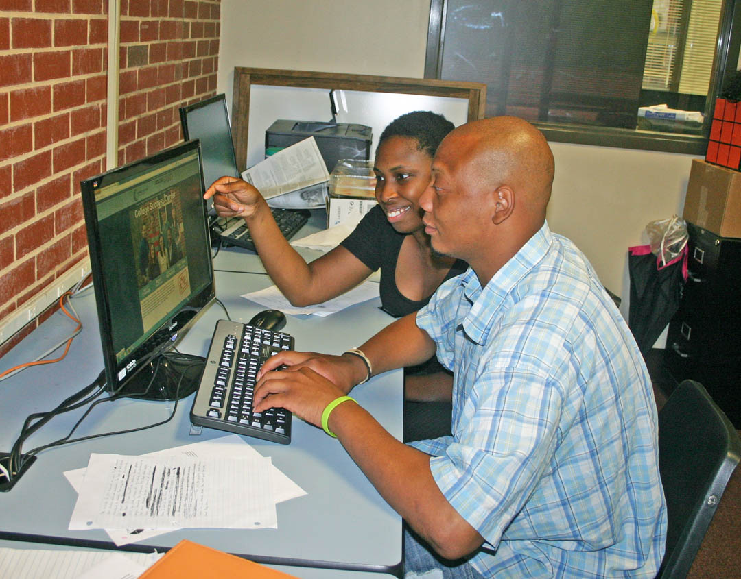 Click to enlarge,  Spencer Bridges (front), of Sanford, a Central Carolina Community College Business Administration major, works with Torry Reynolds, lead success coach, at the college's new College Success Center.
