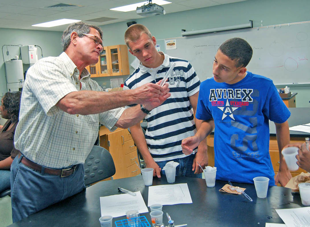 Click to enlarge,  Central Carolina Community College bioprocessing lead instructor Joe Robinson (left) and students Chris Barron, of Western Harnett High School, and Steven Collazo, of  Overhills High School, check out a clump of DNA precipitated in a test tube by adding alcohol to filtered liquefied strawberries. The students were among 52 Harnett County Schools high school students taking part in the college's Upward Bound Math and Science Summer Academy. All visited the college's Lee County Campus the week of June 24-27 to gain hands-on experience with the use of math and science skills in careers such as bioprocessing, chemistry, broadcasting, chromatography, dental hygiene and dental assisting. They also learned more about what college is like and how to prepare to succeed. For more information about Upward Bound Math and Science, call 919-718-7463, email ubms@cccc.edu, or visit the program's website at www.cccc.edu/ubms. For more about Central Carolina Community College classes, visit www.cccc.edu.