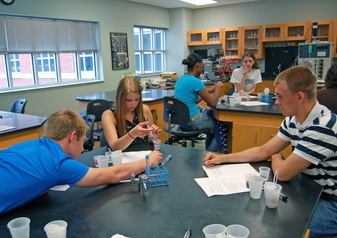 Click to enlarge,  Harnett County Schools students (from left) Zachary Allen, of Harnett Central High School, Brooke Coats, of Triton High School, and Chris Barron, of Western Harnett High School, work together in a bioprocessing laboratory at Central Carolina Community College to precipitate out the red and blue dyes in grape soda.  In the background, (from center) are Maya Davis, of Harnett Central High School, Alexandrea Chavis, of Triton High School, and Shantel Elliot, of Harnett Central High School. The students were among 52 Harnett County Schools high school students taking part in the college's Upward Bound Math and Science Summer Academy. All visited the college's Lee County Campus the week of June 24-27 to gain hands-on experience with the use of math and science skills in careers such as bioprocessing, chemistry, broadcasting, chromatography, dental hygiene and dental assisting. They also learned more about what college is like and how to prepare to succeed. For more information about Upward Bound Math and Science, call 919-718-7463, email ubms@cccc.edu, or visit the program's website at www.cccc.edu/ubms. For more about Central Carolina Community College classes, visit www.cccc.edu.