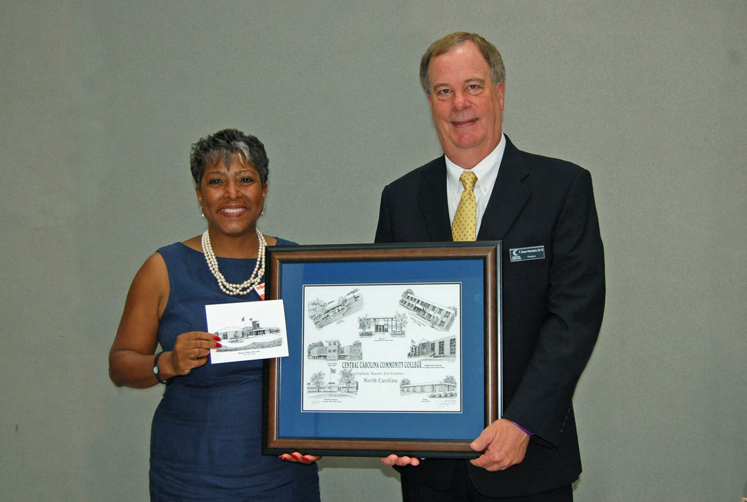 Click to enlarge,  Departing Central Carolina Community College Board of Trustees member Ophelia Livingston (left), of Lee County, was honored at the board's July 24 meeting in the Dennis A. Wicker Civic Center. Livingston, owner of OWL Risk Management, had served as a trustee since 2009. CCCC President Bud Marchant (right) presented her with a Jerry Miller print of college buildings. Departing trustee R.V. Hight, of Lee County, editor of the Sanford Herald, was also honored. He had served on the board since 2005. Departing trustee Douglas Wilkinson Jr., also of Lee County, and president of Wilkinson Cadillac Pontiac GMC, was unable to attend the reception. He was first appointed by Gov. Mike Easley in 2005 and reappointed by Gov. Bev Perdue in 2009. Also completing their terms on the board were Tracy Hanner and George Lucier, of Chatham County, and Tim McNeill, of Harnett County. They will be honored at future board meetings in their counties. For more information about CCCC and its programs, visit www.cccc.edu.