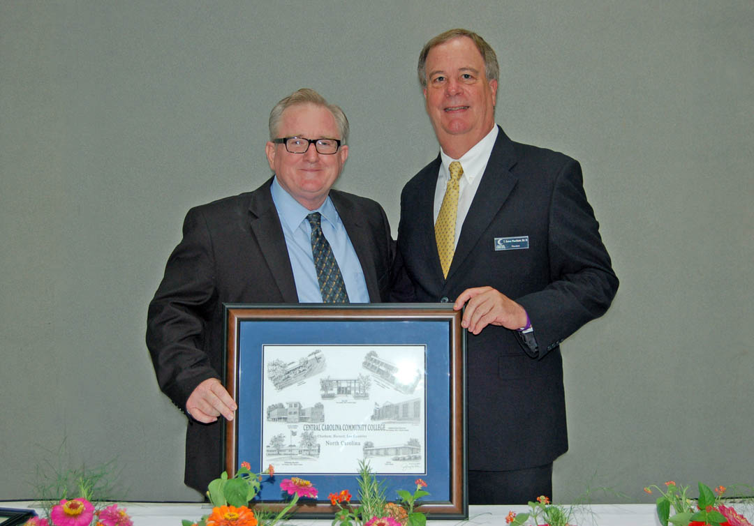 Click to enlarge,  Central Carolina Community College President Bud Marchant (right) presents departing college trustee R.V. Hight, of Lee County, with a Jerry Miller print of college buildings at the board's July 24 meeting in the Dennis A. Wicker Civic  Center. Hight, editor of The Sanford Herald, had served on the board since 2005. Departing trustee Ophelia Livingston, also of Lee County, owner of OWL Risk Management, was also honored. She had served as a trustee since 2009. Departing trustee Douglas Wilkinson Jr., president of Wilkinson Cadillac Pontiac GMC, and also of Lee County, was unable to attend the presentation. He had served as a trustee since 2005. Also completing their terms on the board were Tracy Hanner and George Lucier, of Chatham County, and Tim McNeill, of Harnett County. They will be honored at future board meetings in their counties. For more information about CCCC and its programs, visit www.cccc.edu.